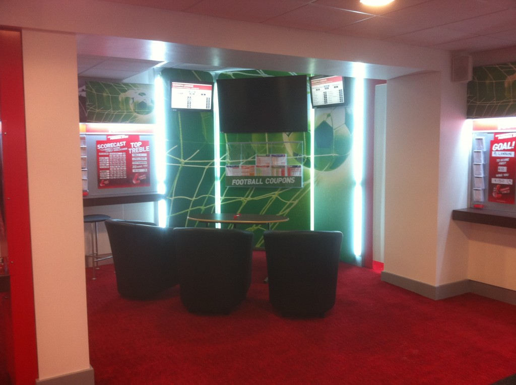 Ladbrokes betting shop with seated area for customers to enjoy live sports betting